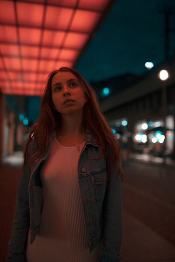 Young woman standing under illuminated lights on footpath at night