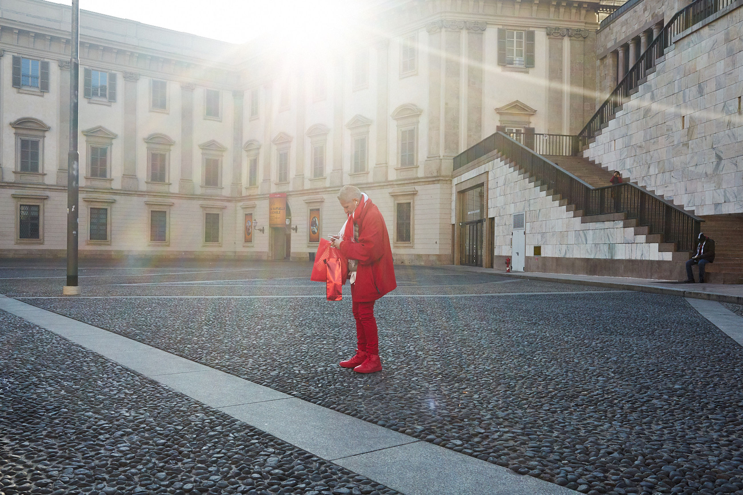 architecture, built structure, building exterior, one person, full length, city, street, real people, red, women, day, lifestyles, warm clothing, coat, walking, lens flare, footpath, leisure activity, sunlight, outdoors