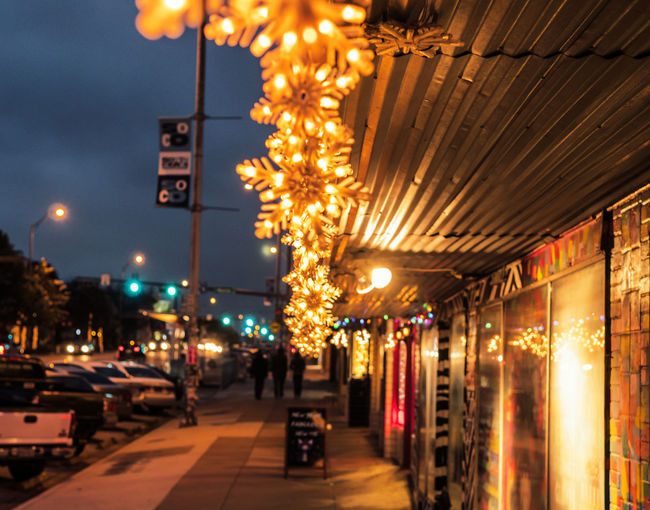 AUSTIN, TEXAS - DECEMBER 31, 2017: Holiday snowflake decorations light up a building along Congress Ave. Holiday Snowflake Lights Architecture Austin, Texas Building Exterior Built Structure Car City Direction Electricity  Illuminated Incidental People Light Lighting Equipment Mode Of Transportation Motor Vehicle Night Outdoors Road Sign Street Street Light The Way Forward Transportation
