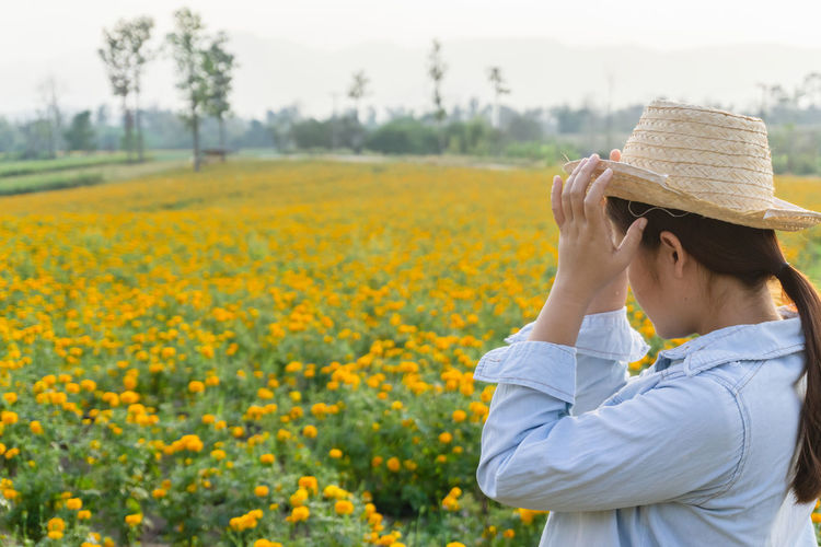Marigold Portrait Flower Marigold Flower Farmer Selective Focus Lifestyles Outdoors Nature Plant Leisure Activity Care Check Hat One Person Real People Beauty In Nature Field Yellow Waist Up Land Flowering Plant Clothing Focus On Foreground Women Growth Day Hair Hairstyle Sun Hat