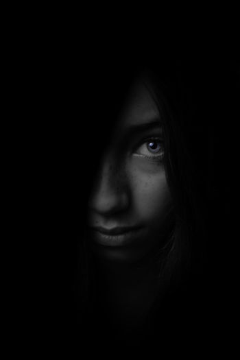 Close-up portrait of a beautiful young woman over black background