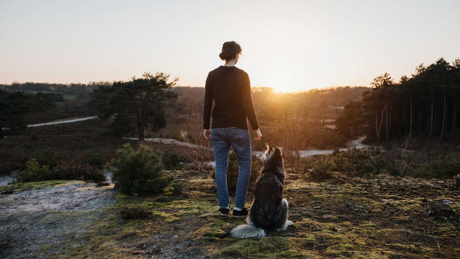 Rear view of woman with dog against sky during sunset