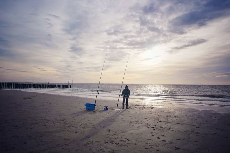 Man with fishing rods on calm beach