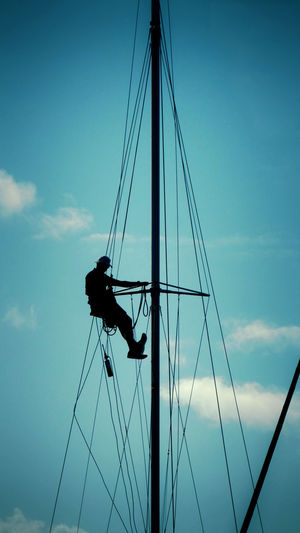 Low angle view of silhouette sailboat against sky