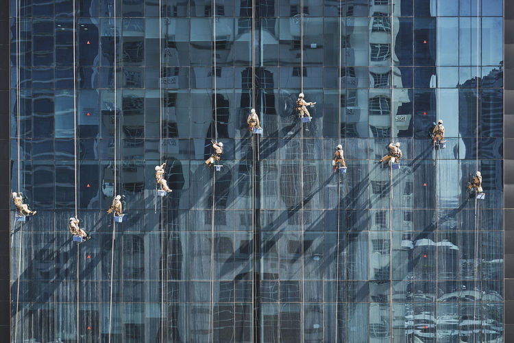Men cleaning glass building