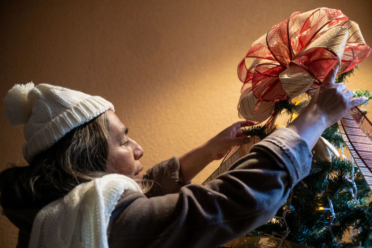 Senior woman putting bow on top of the tree, christmas parties