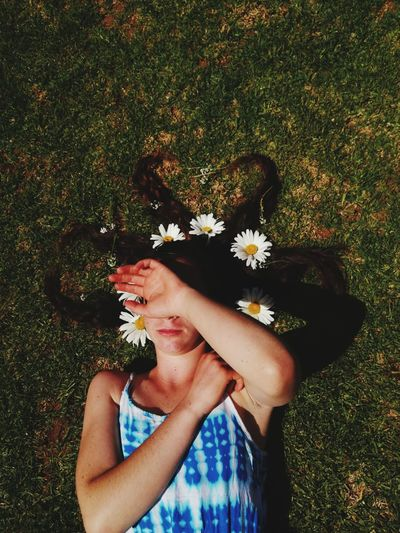 High angle view of woman with flowers on hair lying at field