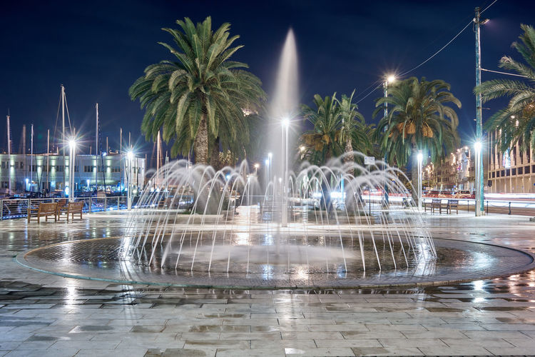 Cagliari, Sardinia Architecture Building Exterior Built Structure City Fountain Illuminated Luxury Motion Nature Night No People Outdoors Palm Tree Plant Reflection Spraying Street Street Light Swimming Pool Travel Destinations Tree Tropical Climate Water