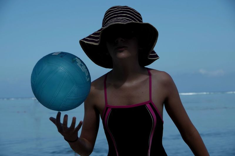 Young woman playing with ball against sea