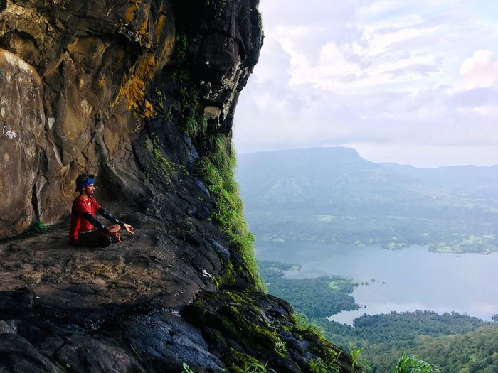 Man meditating while sitting on rock by mountains
