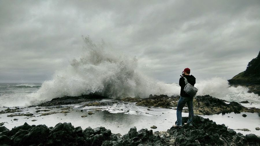 Person Watching Sea Waves Crashing On Shore