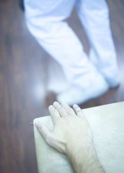 Cropped hand of patient on bed by doctor on parquet floor in hospital