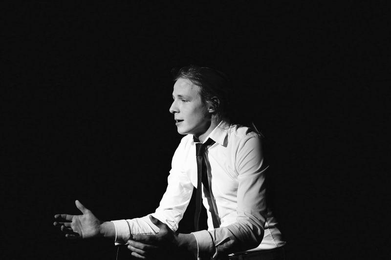 Businessman gesturing while sitting in darkroom