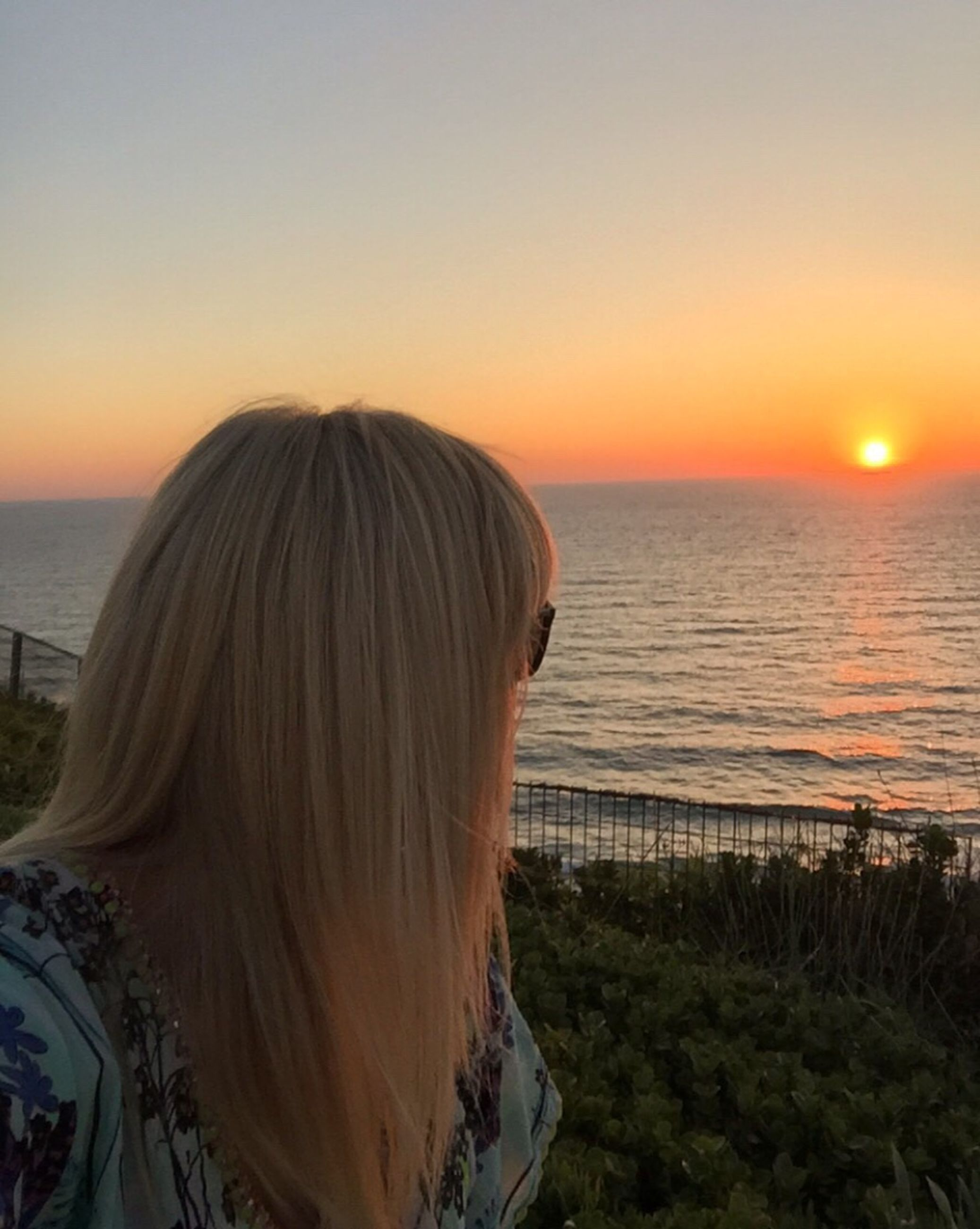 sunset, sea, rear view, horizon over water, water, one person, scenics, clear sky, real people, nature, tranquil scene, beauty in nature, idyllic, sky, tranquility, outdoors, beach, sun, women, leisure activity, lifestyles, day, people