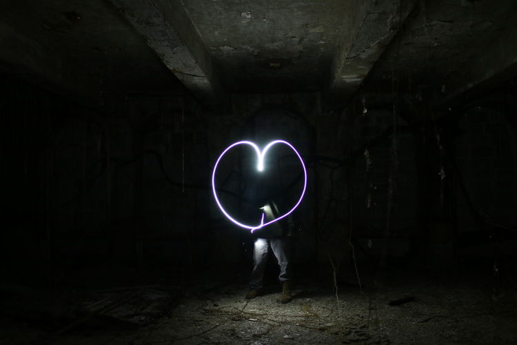 Person Making Heart Shape Through Light Painting In Abandoned Room