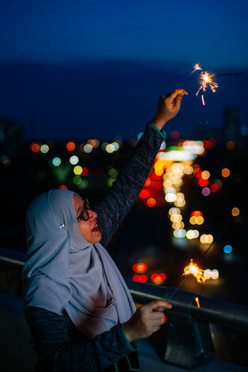 Side view of smiling mid adult woman holding burning sparkler at night