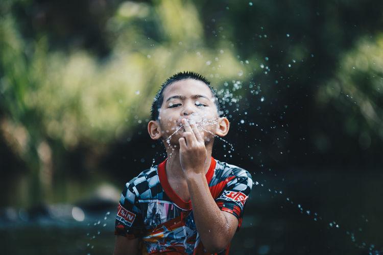 Portrait of boy spitting water