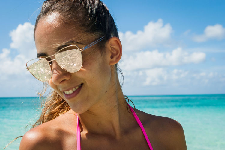 Smiling young woman in sunglasses at beach against sky
