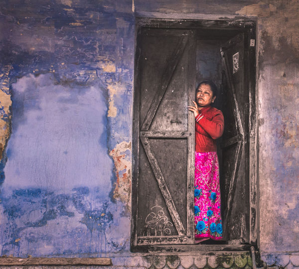 Portrait of smiling young woman standing against door of building