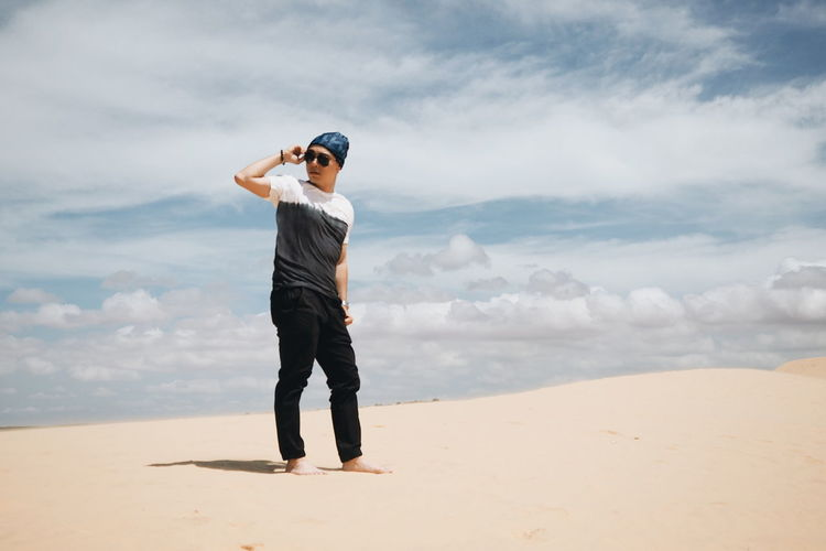 Full length of young man standing on sand against cloudy sky