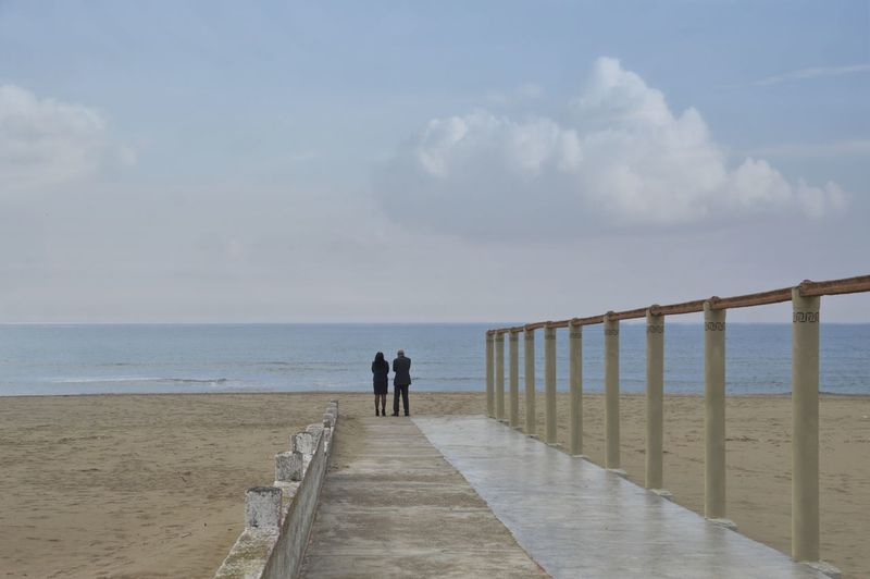 Beach Beauty In Nature Cloud - Sky Couple - Relationship Diminishing Perspective Direction Horizon Horizon Over Water Land Nature Outdoors Railing Rear View Scenics - Nature Sea Sky The Way Forward Tranquil Scene Water