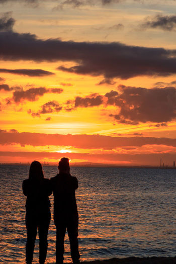 A couple at sunset Beach Beauty In Nature Bonding Cloud - Sky Couple - Relationship Horizon Over Water Men Orange Color Outdoors Positive Emotion Real People Scenics - Nature Sea Silhouette Sky Standing Sunset Togetherness Two People Water Women