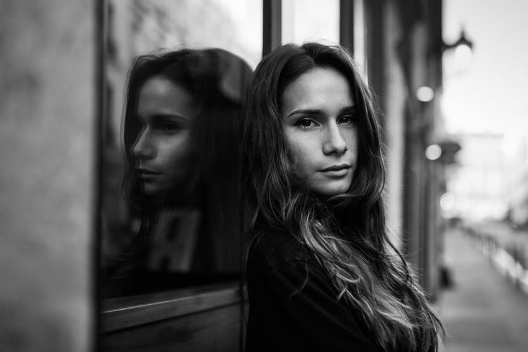 Portrait Of Young Woman Leaning On Window Outdoors