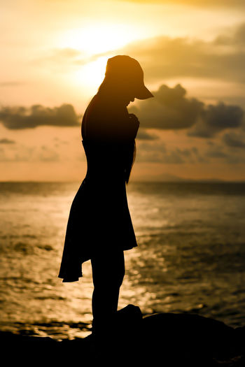 Side view of silhouette woman standing at beach against sky during sunset