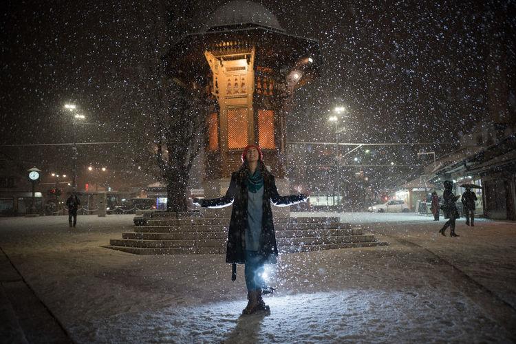 People on wet street at night