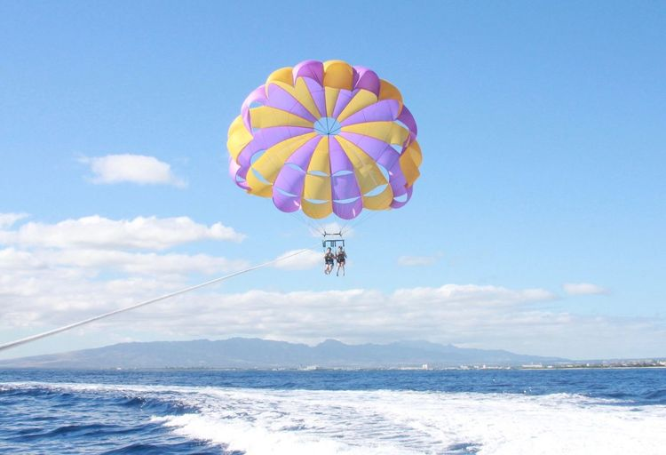 Man and woman paragliding over sea against sky