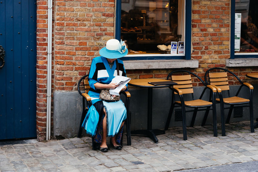 Old refined woman dressed in blue sitting on a terrace in the street of Bruges. Adult Architecture Belgium Blue Bruges Brugge City City Life Cityscapes Day Dress Electricity  Elégance Full Length Hat Lifestyles Old Woman One Person Outdoors People Real People Refined Retro Terrace Women