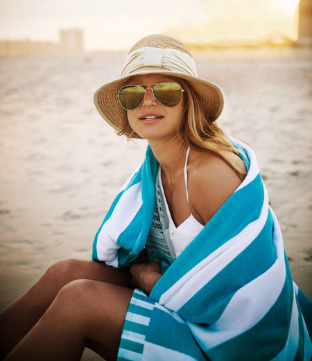 Portrait of woman wearing sunglasses sitting at beach