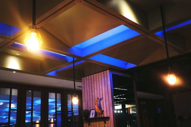 Low angle view of illuminated lights hanging on ceiling at night