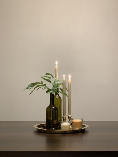 Close-up of illuminated candles on table against wall