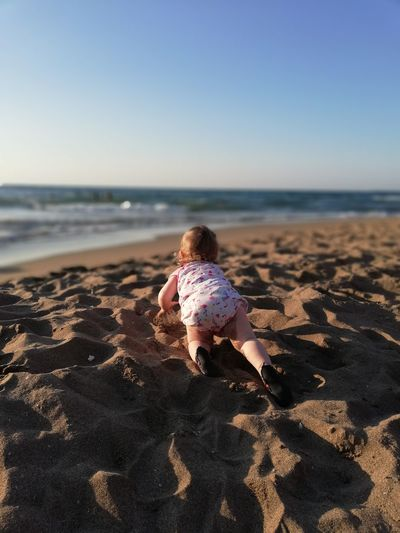 Girl crawling on sand against clear sky