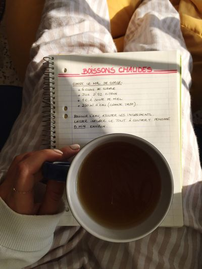 Midsection of woman holding hot drink on spiral notebook