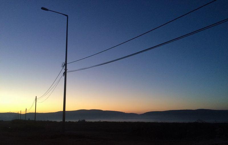 Electricity pylons on landscape at sunset