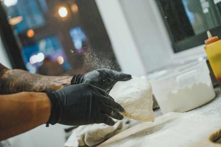 Gloved hands of man working with pizza dough in kitchen