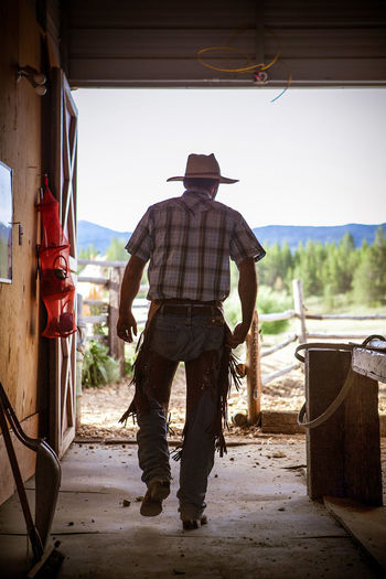 Rear View Of Man Wearing Cowboy Hat At Farm