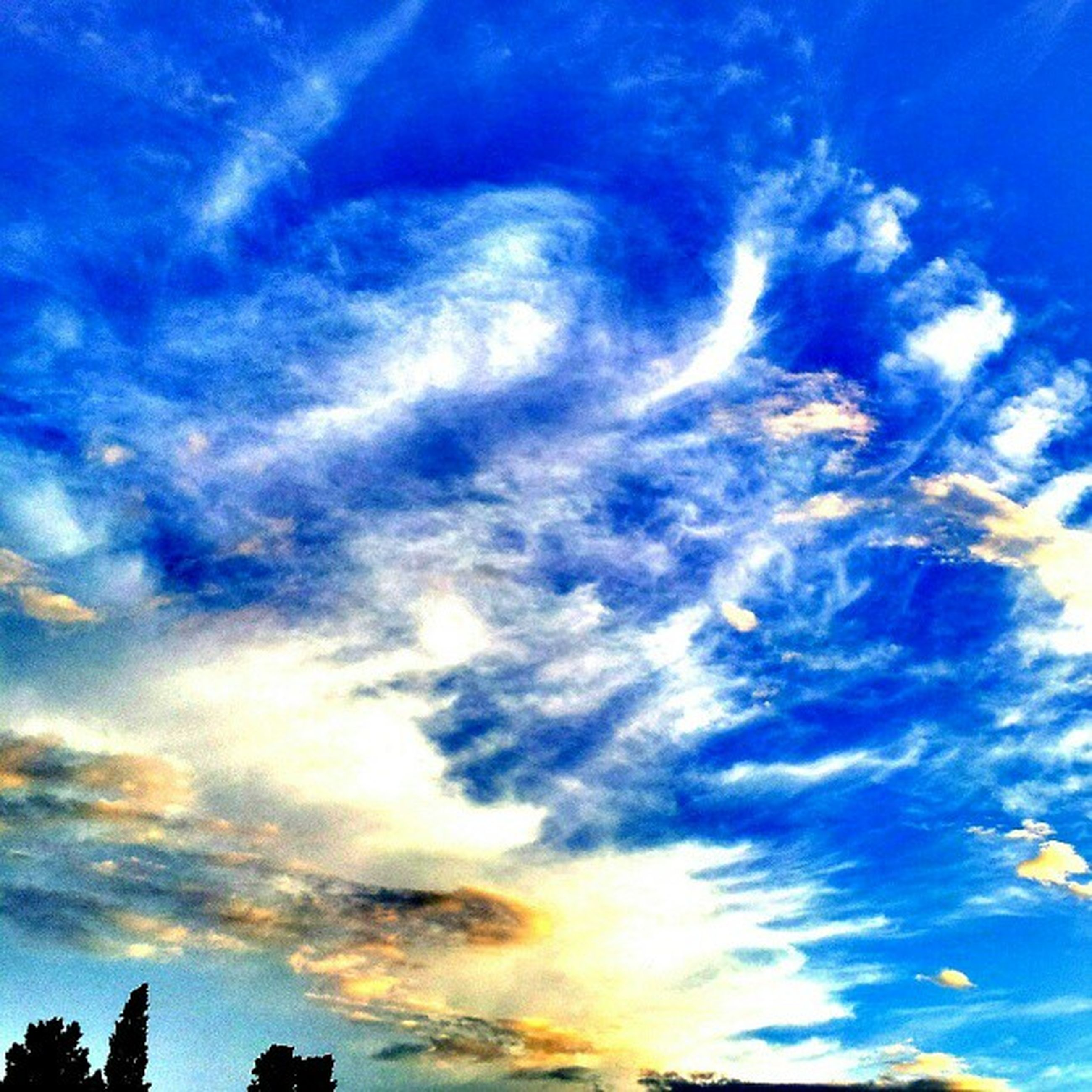 sky, blue, low angle view, cloud - sky, beauty in nature, tranquility, scenics, cloud, nature, tranquil scene, cloudy, cloudscape, sunset, silhouette, idyllic, outdoors, sunlight, no people, backgrounds, majestic