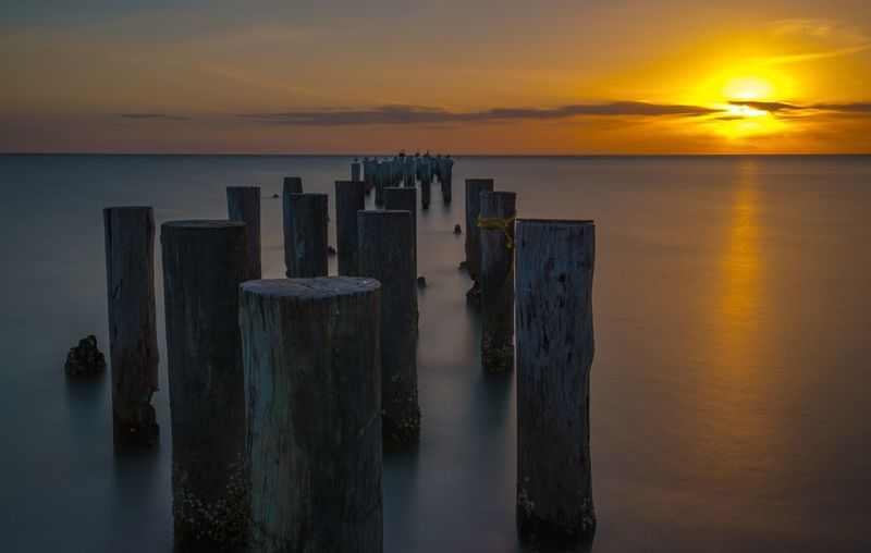 Wooden posts in sea against orange sky during sunset