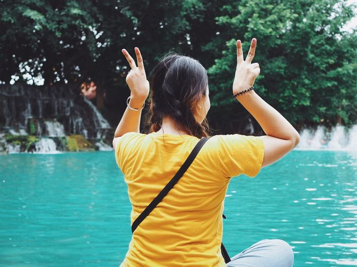 Rear view of woman gesturing peace sign while sitting by swimming pool