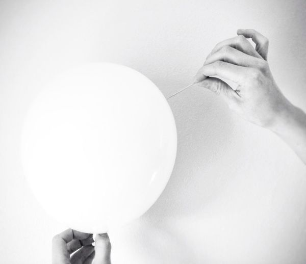 Close-up of hands holding balloon over white background