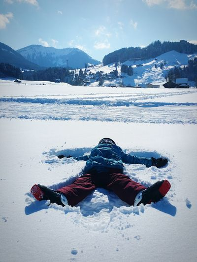 Full Length Of Man Making Snow Angel On Field Against Sky