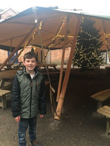 Christmas festivities Tipi With Xmas Tree Christmas Decoration Boys One Person Real People Childhood Smiling Looking At Camera Leisure Activity Portrait Lifestyles Elementary Age Happiness Full Length Day Outdoors Standing Tree Warm Clothing