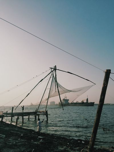 Silhouette fishing net on shore against clear sky