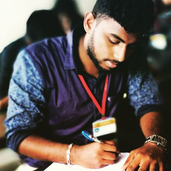 Young Man Writing Exam In Classroom