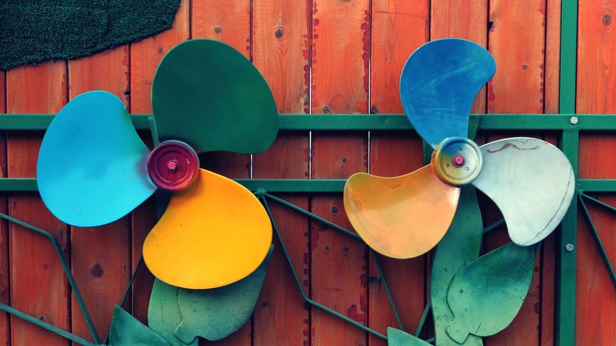 Close-up of colorful electric fans decorated on wall