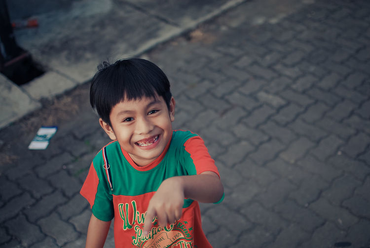 High angle portrait of smiling boy standing on street in city