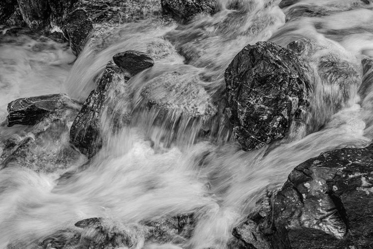 Blurred motion of water over rocks in mountain river